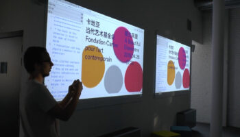 Louis Hoebregts speaking in front of two large screens with blobs shapes and Chinese characters on the screens.