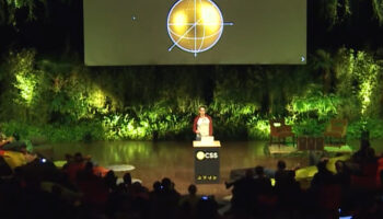 Louis Hoebregts speaking in front of an audience on a jungle themed stage. On the screen behind, a Christmas decoration with CSS Christ Math written above.